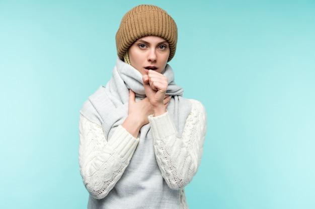 Erkältung und grippe-porträt der schönen jungen frau mit husten und halsschmerzen, die sich krank fühlen innenaufnahme nahaufnahme der kranken ungesunden frau im schal husten