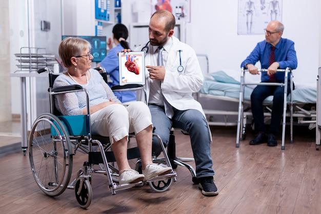 Erklärung der koronaren herzkrankheit vom arzt für eine behinderte ältere frau im rollstuhl während der ärztlichen untersuchung