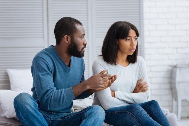 Erläuterung. emotionale junge frau, die beleidigt aussieht, während ihr freund ihr die situation erklärt