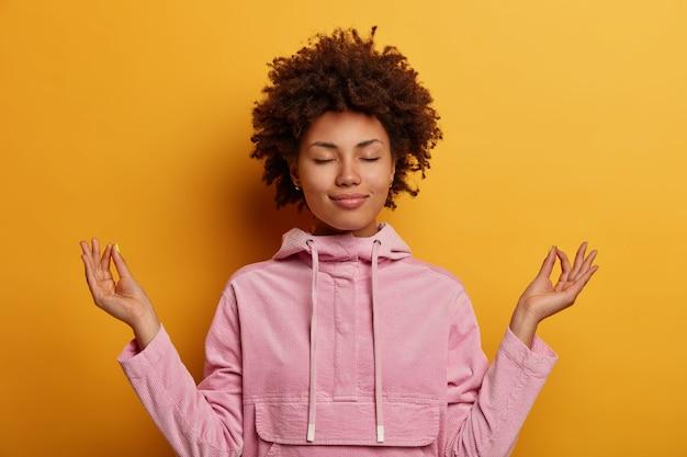 Erleichterte ethnische frau steht in lotus-pose, versucht während der quarantäne oder des lockdowns zu meditieren, erreicht das nirvana, macht yoga, hält die augen geschlossen und trägt ein sweatshirt. psychische gesundheit, entspannung, lebensstil