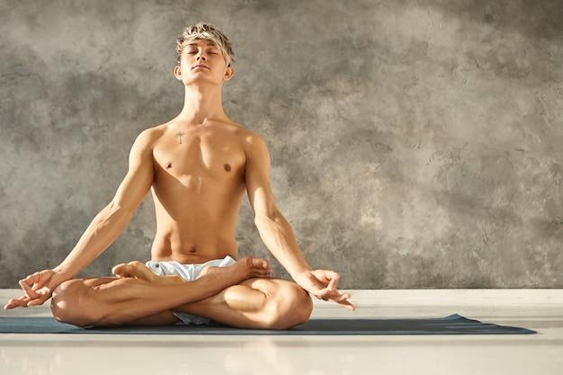 Erleuchteter junger kaukasischer mann, der hemdlos und barfuß im fitnessstudio posiert, ruhigen friedlichen gesichtsausdruck hat, mit geschlossenen augen meditiert, auf matte in lotushaltung sitzt, hände in mudra-geste