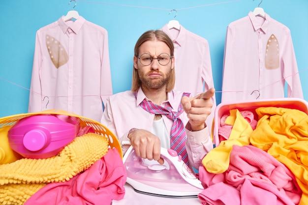 Ermüdeter hausmann, der damit beschäftigt ist, wäsche zu hause zu bügeln, posiert mit elektrischen eisenkörben voller schmutziger wäsche und waschmittel, trägt hemdkrawatte hat einen mürrischen gesichtsausdruck isoliert auf blauem hintergrund