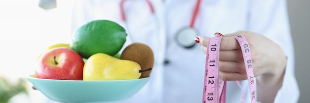 Ernährungsberater arzt hält obstteller und zentimeter richtiges ernährungs- und lifestyle-konzept