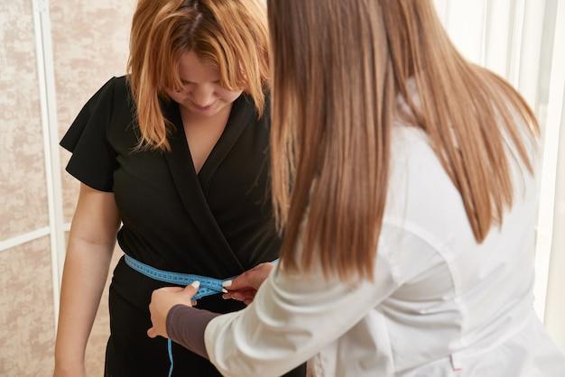 Ernährungsberater, der teenager mit klebeband in der gewichtsverlustklinik misst