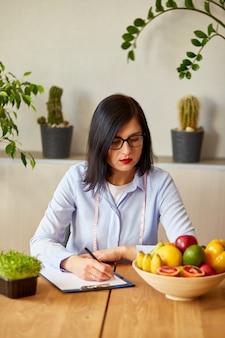 Ernährungsberaterin, diätassistentin, die einen ernährungsplan schreibt, mit gesundem gemüse und obst, gesundheits- und ernährungskonzept. ernährungsberaterin mit früchten, die an ihrem schreibtisch arbeiten.