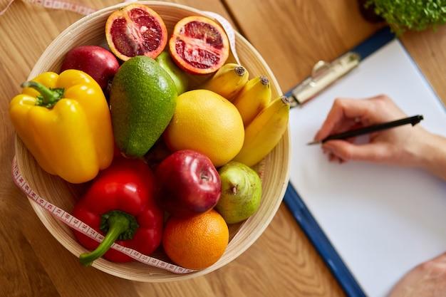 Ernährungsberaterin, diätassistentin, die einen ernährungsplan schreibt, mit gesundem gemüse und obst, gesundheits- und ernährungskonzept. ernährungsberaterin mit früchten, die an ihrem schreibtisch, arbeitsplatz arbeiten