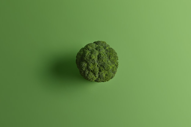 Ernährungsgesunder brokkoli, der von oben auf grünem hintergrund fotografiert wird. leckeres gemüse kann roh und gekocht gegessen werden. quelle von vitaminen. koch- und essenskonzept. nährstoffreiche kohlsorte