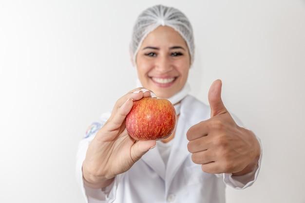 Ernährungswissenschaftler der jungen frau, der eine apfelfrucht hält. frau doktor
