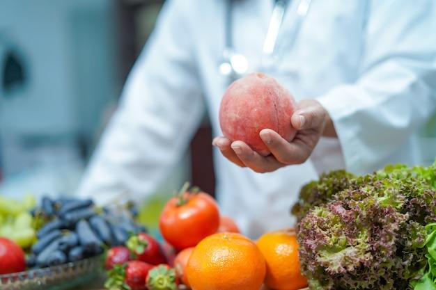 Ernährungswissenschaftlerdoktor, der in der hand früchte hält.