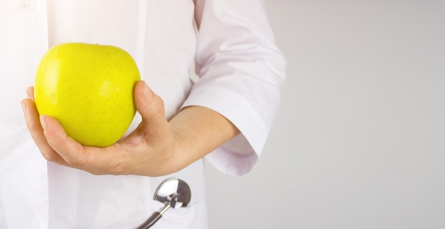 Ernährungswissenschaftlerdoktor hand auf hüfte, die grünen apfel zeigt. die hand des ernährungswissenschaftlerdoktors, die einen frischen grünen apfel hält gesunde ernährung.