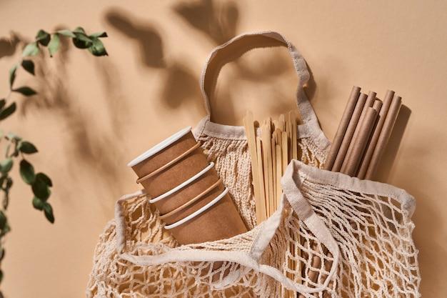 Erneuerbare einzelobjekte für den heimgebrauch, bambus- oder papierstrohhalme, einwegbecher und hölzerne kaffeerührer auf beige mit schatten von den blättern am strand. kein verlust. umweltverschmutzung