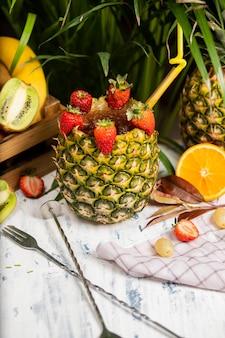 Erneuernder alkoholischer cocktail margarita des sommers mit zerquetschtem eis und zitrusfrüchten innerhalb der ananas mit erdbeeren auf küchentisch