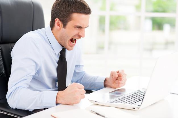 Erneut fehlgeschlagen. wütender junger mann in hemd und krawatte, der auf den computermonitor schaut und schreit, während er an seinem arbeitsplatz sitzt