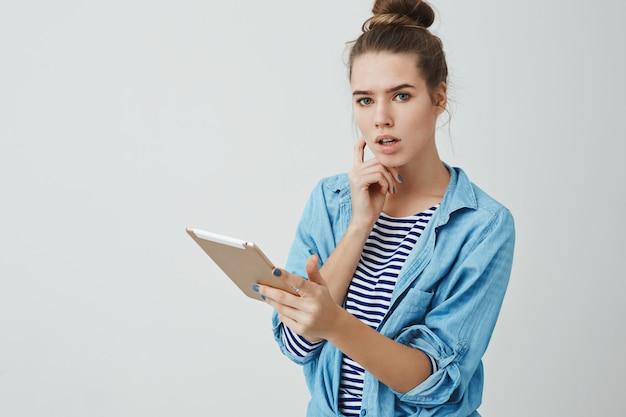 Ernst aussehende frau mittlere arbeit, die digitalen tablet-beratungsassistenten nachdenklich aussehend hält