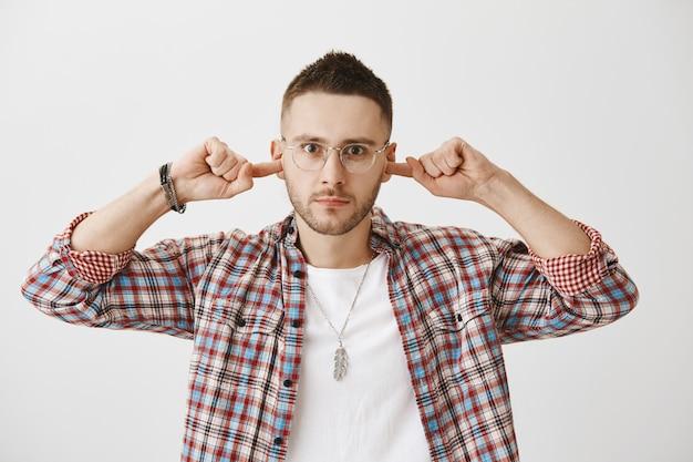 Ernst besorgter junger mann mit brille posiert