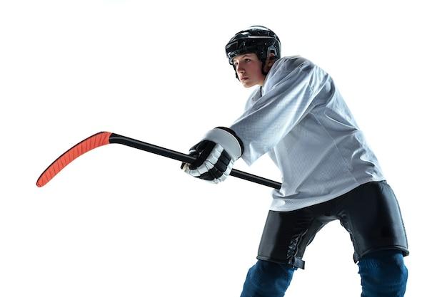 Ernst. junger männlicher hockeyspieler mit dem stock auf eisplatz und weißer wand. sportler tragen ausrüstung und helm üben. konzept von sport, gesundem lebensstil, bewegung, bewegung, aktion.