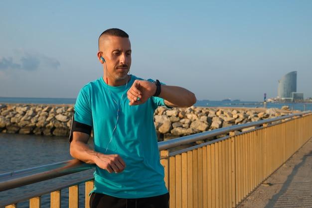Ernst männlichen jogger blick auf die uhr auf der brücke