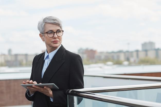 Ernst reife geschäftsfrau in brillen, die mit nachdenklichem anblick wegschauen, während sie digitales tablett im freien verwenden