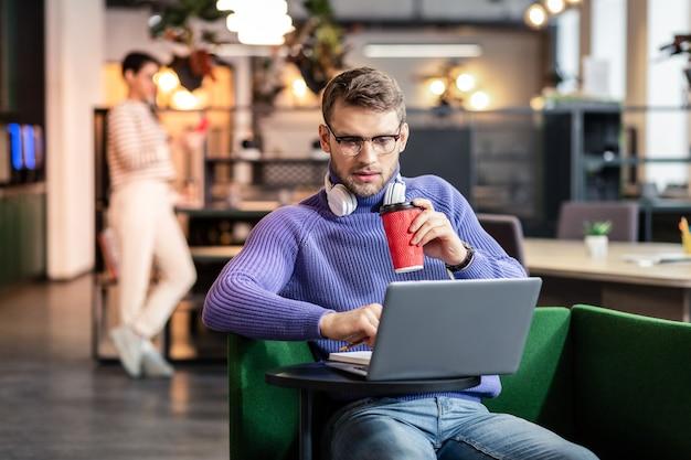 Ernst sein. hübsche männliche person, die auf gemütlichem stuhl sitzt und an seinem projekt arbeitet
