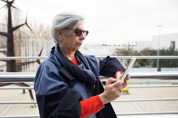 Ernste ältere frau in der sonnenbrille unter verwendung der tablette draußen