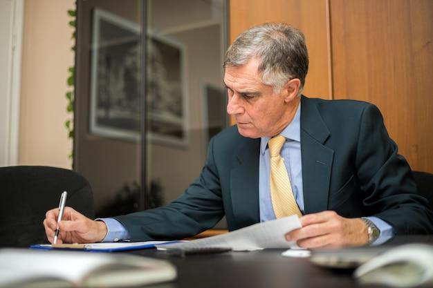 Ernste ältere geschäftsmannlesegeschäftsunterlagen im büro. senior manager, der angebot der firma für vertrag wiederholt.