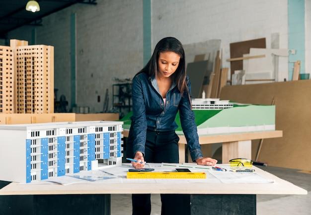 Ernste afro-amerikanische dame mit dem stift, der nahes modell des gebäudes auf tabelle steht