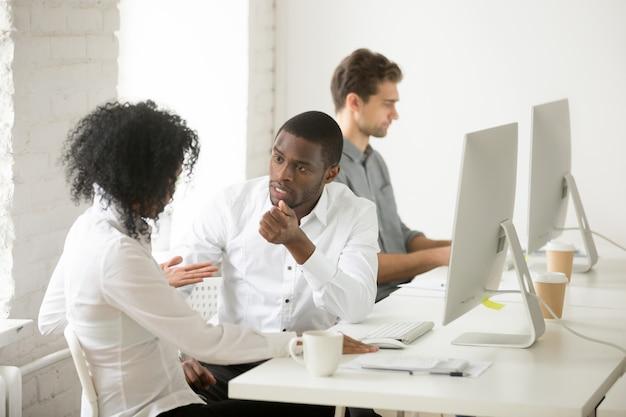 Ernste afroamerikanerkollegen, die zusammen projekt am arbeitsplatz besprechen sprechen