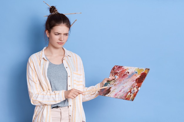 Ernste ar traurige frau mit palette in den händen, dame gemischte farben, künstlerin, die lässige kleidung trägt, die farbpalette betrachtet