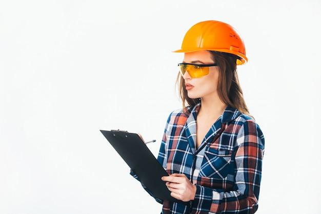 Ernste architektenfrau mit schutzhelm