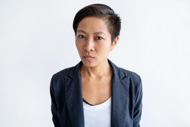 Ernste asiatische geschäftsfrau, die kamera betrachtet