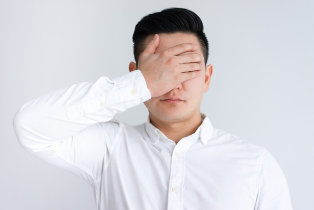 Ernste asiatische mannbedeckungsaugen mit der hand