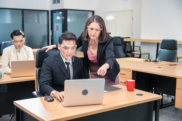 Ernste asiatische weibliche exekutivberatung mit männlichem kollegen, der gesichtsschutz trägt, der mit laptop am schreibtisch im modernen büro arbeitet