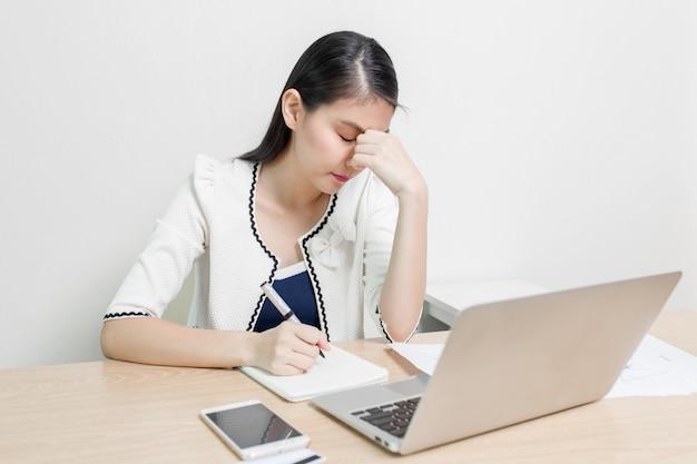 Ernste asiatische weibliche exekutive, die ideen beim arbeiten an ihrem schreibtisch mit laptop findet