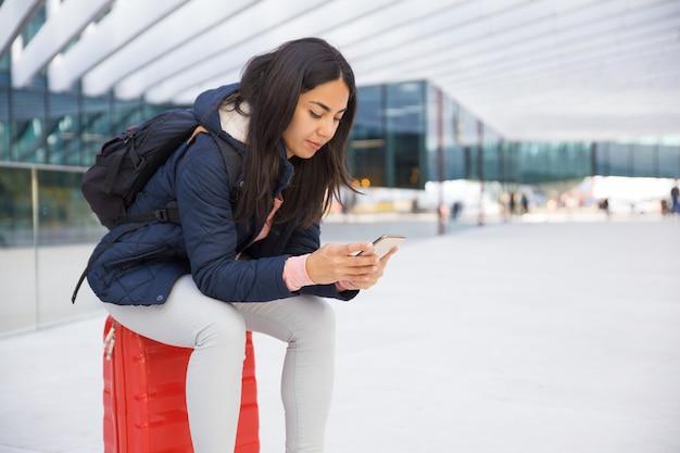 Ernste beschäftigte junge frau, die smartphone im flughafen verwendet