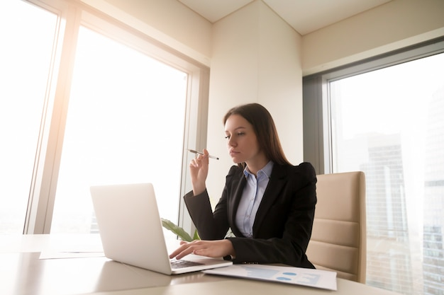 Ernste betroffene junge geschäftsfrau, die am schreibtisch unter verwendung des laptops arbeitet