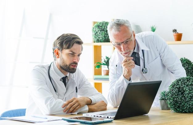 Ernste doktoren, die laptopschirm betrachten