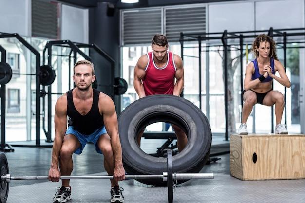 Ernste drei muskulöse anhebende und springende leute