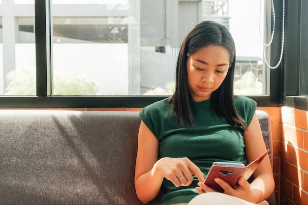 Ernste frau benutzen ihren smartphone auf dem sofa in der ecke des cafés.