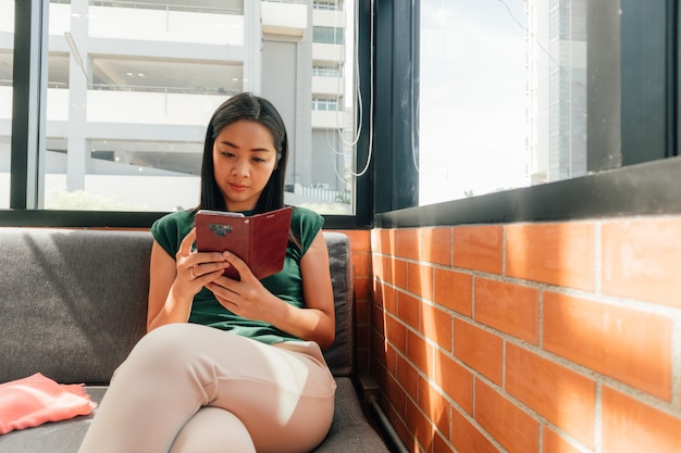 Ernste frau benutzen ihren smartphone auf dem sofa
