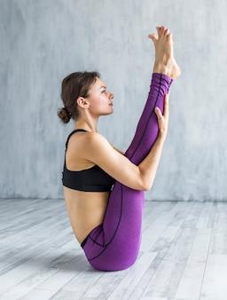 Ernste frau, die in einer yogastellung sitzt