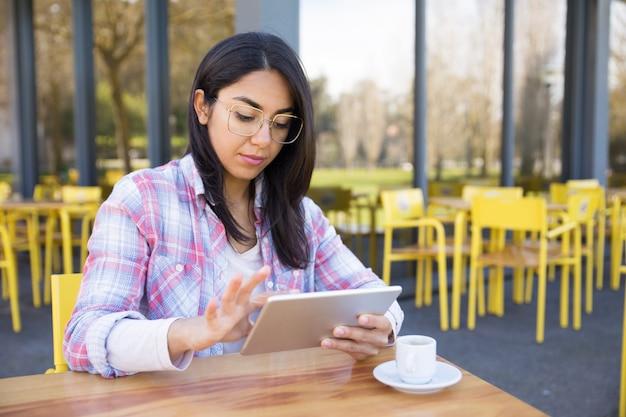 Ernste frau, die tablette verwendet und kaffee im café trinkt