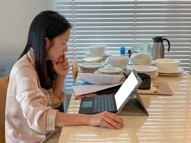Ernste frau im pyjama, die am laptop am esstisch arbeitet