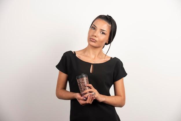 Ernste frau mit tasse kaffee, die auf weißer wand aufwirft.