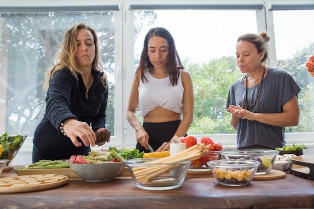 Ernste frauen, die gemüse am küchentisch kochen