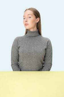 Ernste geschäftsfrau, die am tisch auf einem blauen studiohintergrund sitzt.