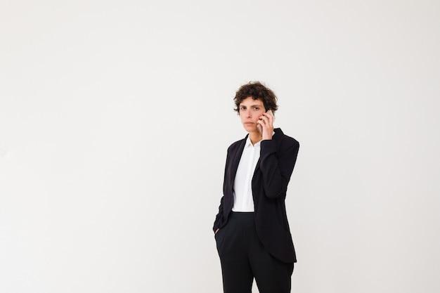 Ernste geschäftsfrau, die durch handy spricht
