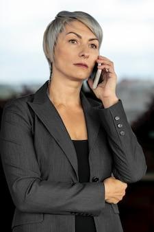 Ernste geschäftsfrau, die über telefon spricht