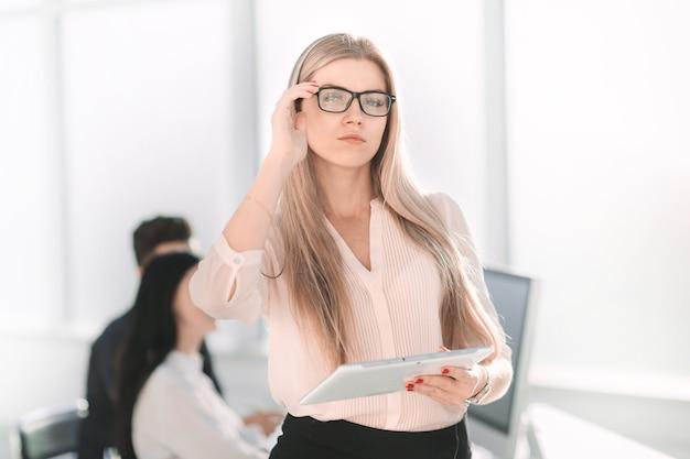 Ernste geschäftsfrau mit digitalem tablett, das nahe schreibtisch steht