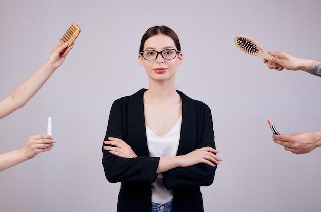 Ernste geschäftsfrau steht auf einer grauen rückseite in einer schwarzen jacke, in einem weißen t-shirt und in einer computerbrille. ihre arme verschränkt. die falschen hände geben ihr zwei kämme und zwei lippenstifte.