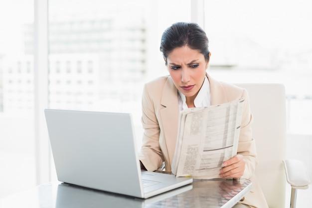 Ernste geschäftsfraulesezeitung beim arbeiten an laptop